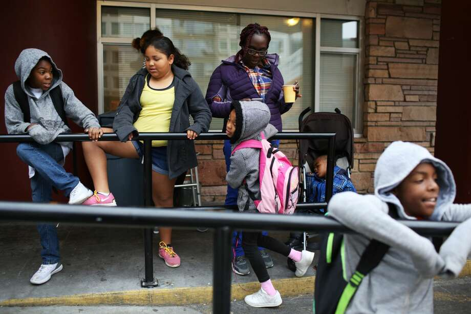 Dee waits outside of Mary's Place with her four children, ages 3, 7, 9 and 11, and a neighbor's daughter, for taxis to pick up the kids and take them to school in the morning. Dee, whose name has been changed for her safety, left her job and all of her belongings and moved her kids to Seattle to escape an abusive relationship. Since arriving here a month ago, a housing situation fell through and she and her family were left homeless. They are now living at Mary's Place homeless shelter. (Genna Martin, seattlepi.com) Photo: GENNA MARTIN, SEATTLEPI.COM