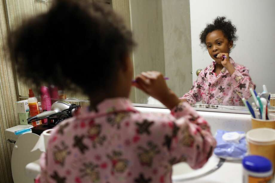 Seven-year-old L. brushes her teeth as she gets ready for school in the morning. (Genna Martin, seattlepi.com) Photo: GENNA MARTIN, SEATTLEPI.COM