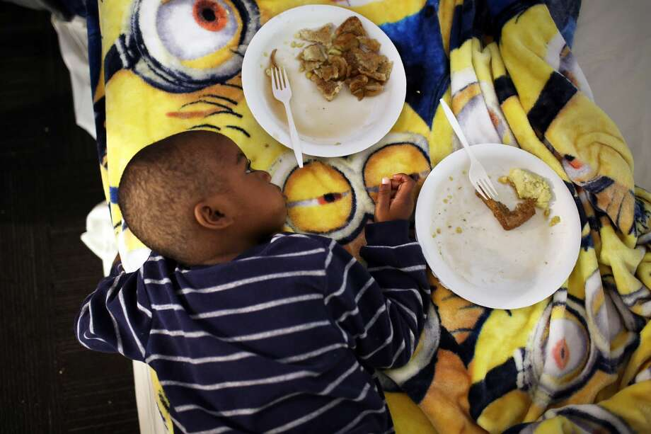 Dee's youngest son, three-year-old S. (who we are calling by his first initial), lies on a mattress while eating breakfast around 7 a.m. (Genna Martin, seattlepi.com) Photo: GENNA MARTIN, SEATTLEPI.COM