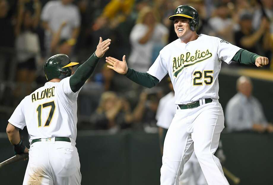 OAKLAND, CA - JUNE 16:  Ryon Healy #25 and Yonder Alonso #17 of the Oakland Athletics celebrates after they both scored on a bases loaded rbi two-run single from Matt Chapman #26 against the New York Yankees in the bottom of the eighth inning at Oakland Alameda Coliseum on June 16, 2017 in Oakland, California. The hit was Chapman's first career base hit. Photo: Thearon W. Henderson, Getty Images