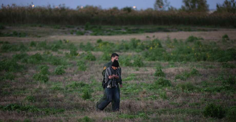 A Custom and Border Patrol officer walks with an undocumented immigrant from Guatemala who was found hiding in the tall grass just south of the border wall near Weslaco, TX,  Thursday, Jan. 16, 2014. Photo: Bob Owen, Staff / San Antonio Express-News / ©2013 San Antonio Express-News