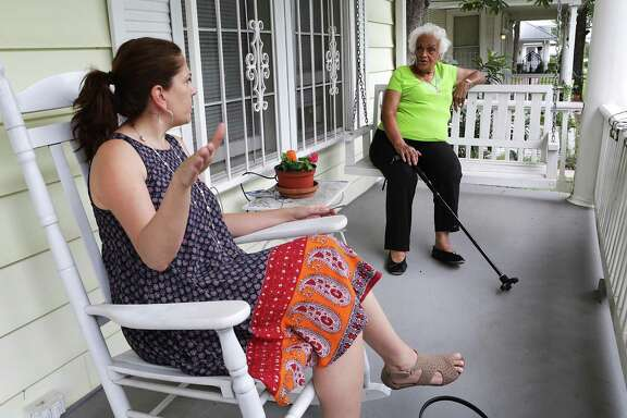Betty Green (right) a longtime resident of Dignowity Hill on North Pine, speaks with neighbor Anita Lubke who moved to the area just over a year ago, as they sit on her front porch June 14.