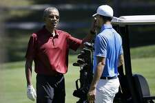 President Barack Obama speaks with NBA basketball player Stephen Curry, of the Golden State Warriors, while golfing, Friday, Aug. 14, 2015, at Farm Neck Golf Club, in Oak Bluffs, Mass., on the island of Martha's Vineyard. The president, first lady Michelle Obama, and daughter Sasha are vacationing on the island. (AP Photo/Steven Senne)