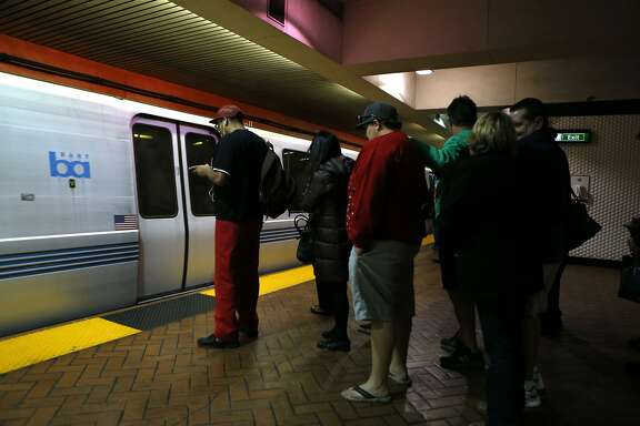 Commuters wait for a train to stop at Powell Street BART station in San Francisco, Calif., on Wednesday, November 26, 2014.