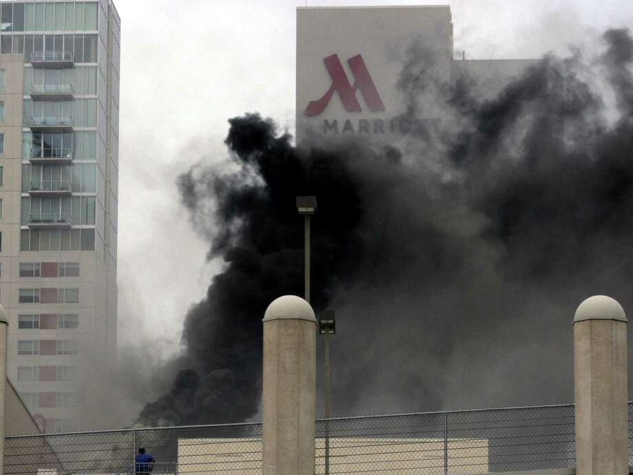 A fire that sparked at a River Walk restaurant Tuesday morning forced hundreds to evacuate as smoke poured into the downtown area from the Shops at Rivercenter. Photo: Juanito M Garza, San Antonio Express-News / San Antonio Express-News / San Antonio Express-News