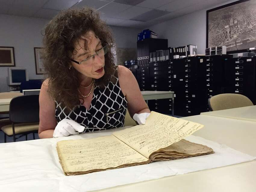 Historian Tricia Barbagallo looks through the Colonial-era Adgate ledger at the Albany County Hall of Records, which she helped rescue after she tipped off investigators when she saw it for sale illegally on eBay. (Paul Grondahl / Times Union)