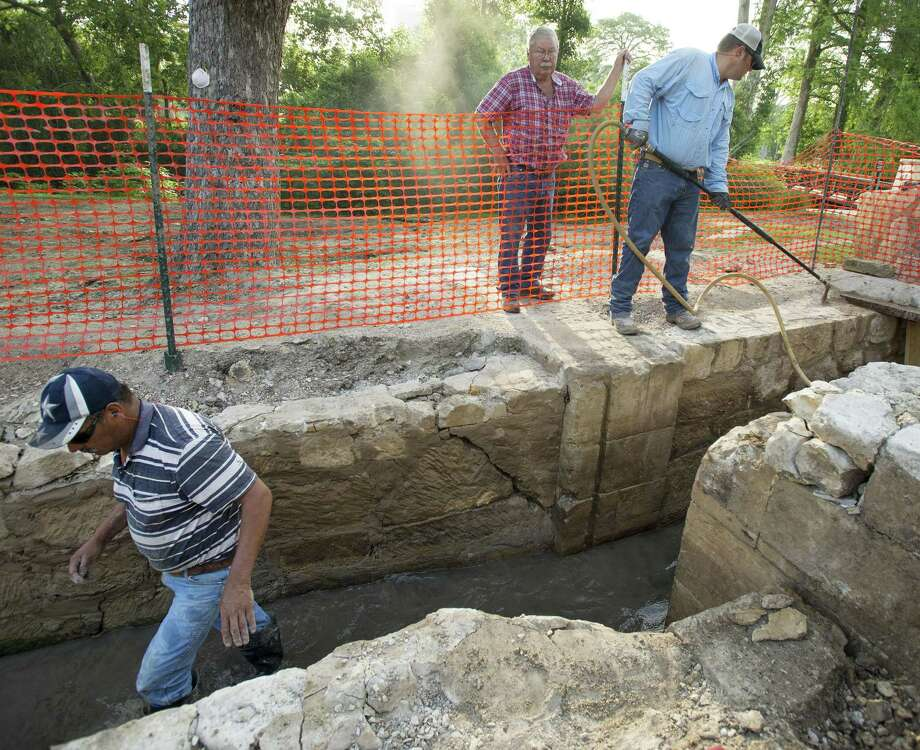 Excavators Filemon Gallegos (from left), Ray Smith and Rud Krisch clear material from a circa 1904 sluice gate that was added to features that fed the Upper Labor Acequia, which was constructed in the 1770s. It is thought that the sluice gate, shown during a 2013 excavation in Brackenridge Park, sits atop the original Spanish colonial structure. Photo: Express-News File Photo / San Antonio Express-News