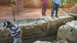 Excavators Filemon Gallegos (from left), Ray Smith and Rud Krisch clear material from a circa 1904 sluice gate that was added to features that fed the Upper Labor Acequia, which was constructed in the 1770s. It is thought that the sluice gate, shown during a 2013 excavation in Brackenridge Park, sits atop the original Spanish colonial structure.