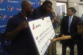 Texans' Johnathan Joseph and Jadeveon Clowney present $10,000 check from Carnival Cruise Lines to Boys and Girls Club of Houston on Tuesday.