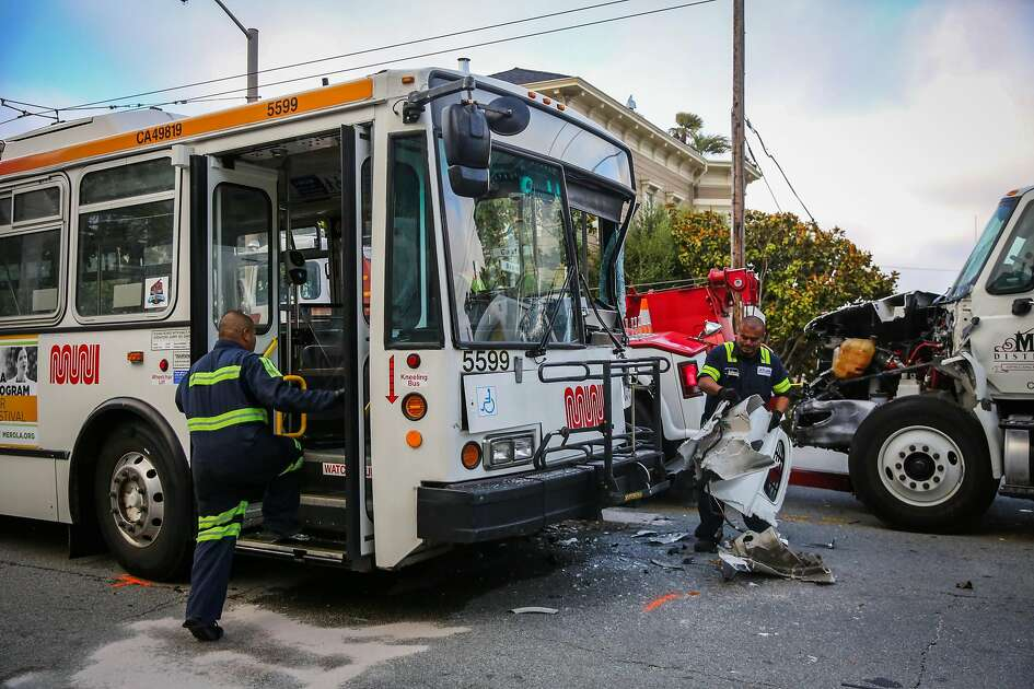 Workers from Atlas Towing Company organize debris before removing vehicles from the scene of a crash between a truck and a Muni bus at Castro and Beaver Streets in San Francisco, California, on Tuesday, June 27, 2017.
