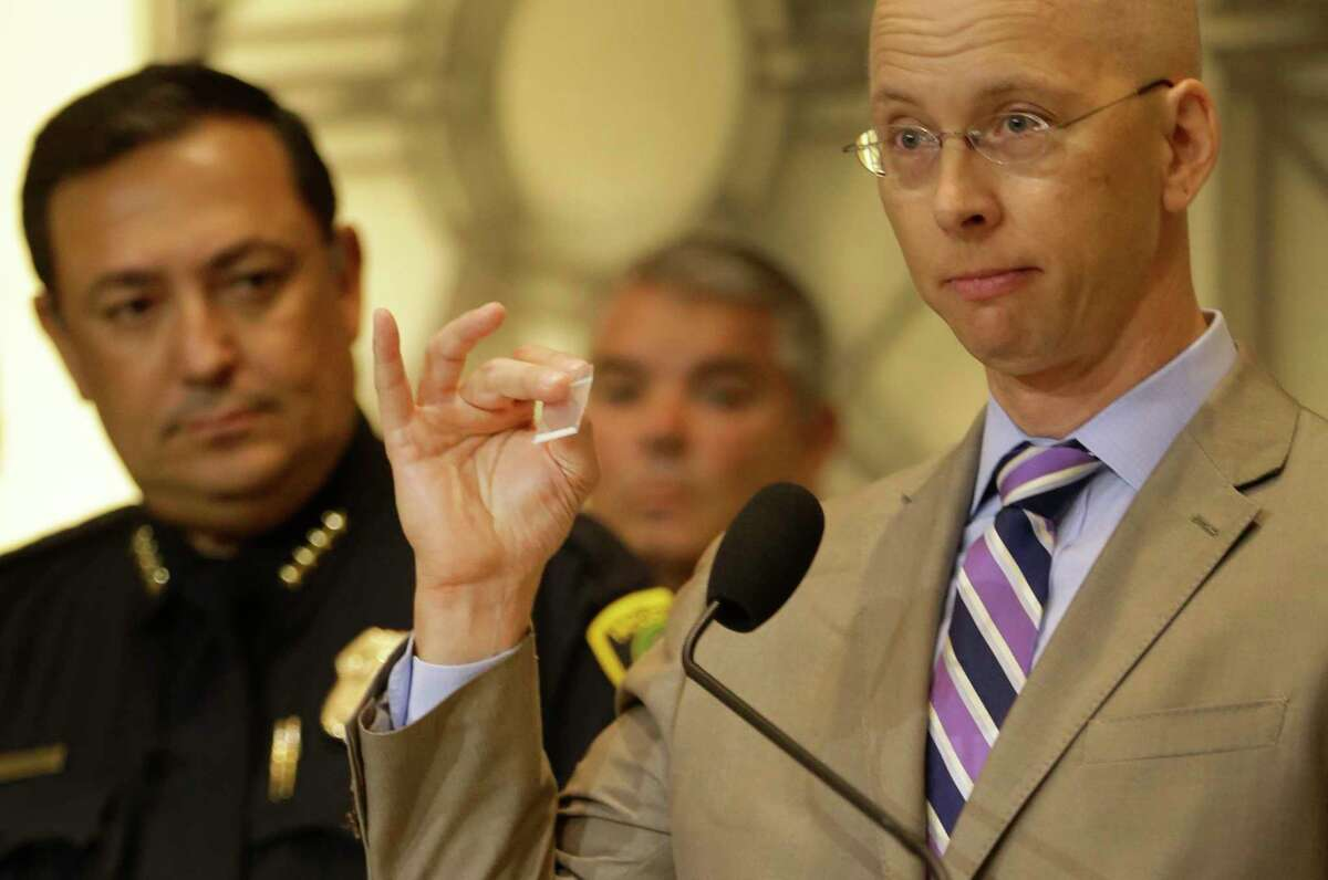 Houston Police Dept. Chief Art Acevedo, left, listens as Dr. Peter Stout, right, Houston Forensic Science Center CEO and president, speaks during a media conference to discuss the seizure of a highly potent synthetic opioid in Houston held at City Hall Tuesday, June 27, 2017, in Houston. He is holding a small bag of sugar to demostrate the amount of 80 milligrams of carfentanil that was seized. That amount could kill 4,000 people.