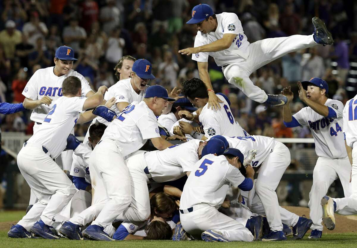 Florida players including center fielder Nick Horvath (26) celebrate after defeating LSU in Game 2 to win the NCAA College World Series baseball finals in Omaha, Neb., Tuesday, June 27, 2017. (AP Photo/Nati Harnik)