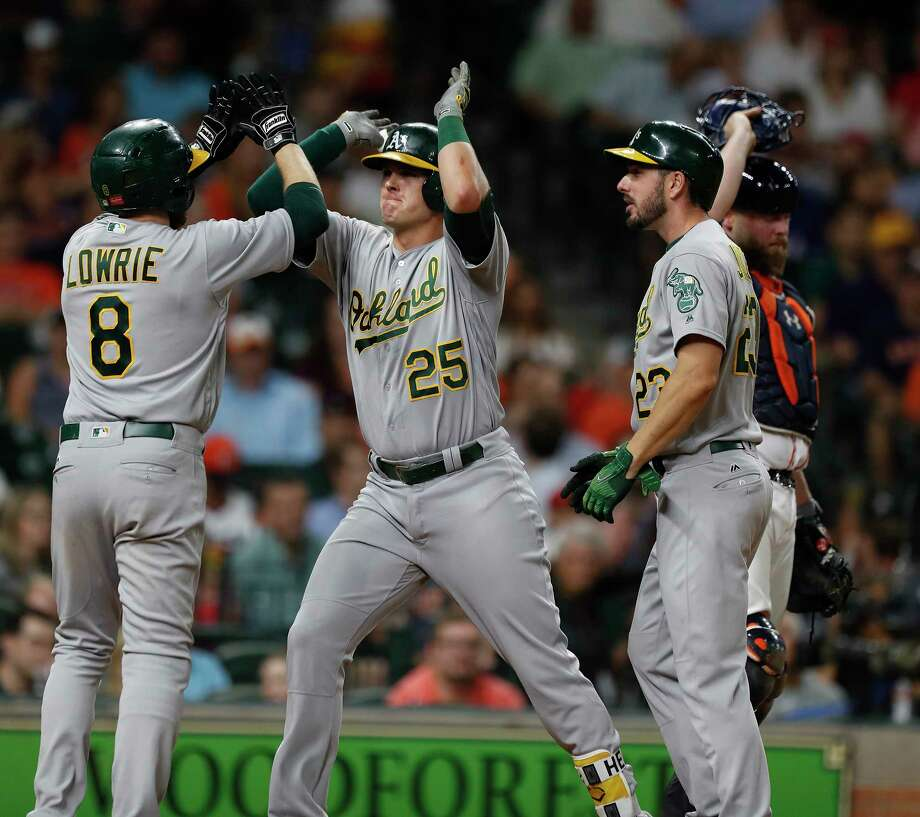 Former Astro Jed Lowrie was the first to greet Athletics teammate Ryon Healy (25) after Healy broke a 1-1 tie with a sixth-inning grand slam. Photo: Karen Warren, Staff Photographer / 2017 Houston Chronicle