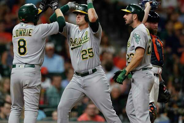 Former Astro Jed Lowrie was the first to greet Athletics teammate Ryon Healy (25) after Healy broke a 1-1 tie with a sixth-inning grand slam.