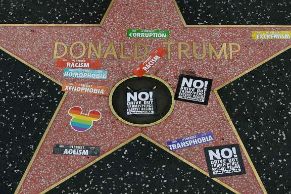 Gay pride stickers placed on the Hollywood Walk of Fame Star of President Donald Trump before the start of #ResistMarch during the 47th annual LA Pride Festival in Hollywood, California on June 11, 2017. Inspired by the huge women's marches that took place around the world following the inauguration of President Trump, LA Pride has replaced its decades-old parade with a protest march. / AFP PHOTO / Mark RALSTONMARK RALSTON/AFP/Getty Images