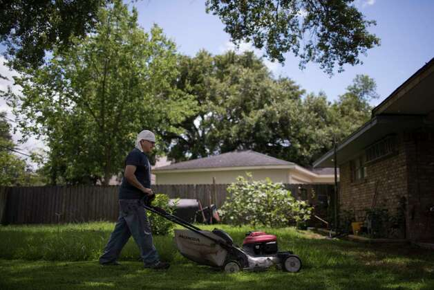 Juan Rodriguez, 47, mows the lawn of his home in Houston, Tuesday, June 27, 2017, while wearing a ankle bracelet tracking device required by Immigration and Customs Enforcement (ICE) authorities who granted Juan prosecutorial discretion. Photo: Marie D. De Jesus, Houston Chronicle / © 2017 Houston Chronicle