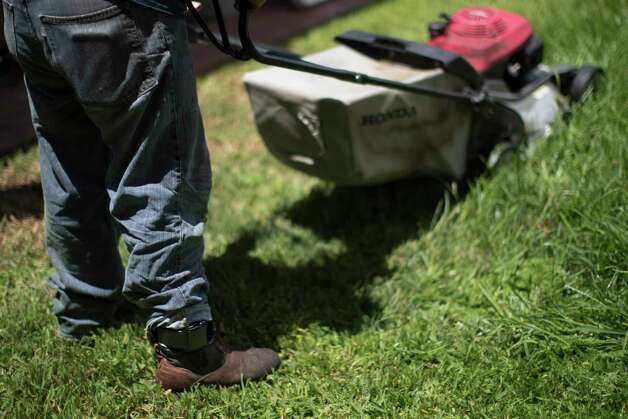 Juan Rodriguez, 47, takes a break from mowing the lawn of his home, Tuesday, June 27, 2017, in Houston, wearing a bracelet ankle monitoring tracker. Photo: Marie D. De Jesus, Houston Chronicle / © 2017 Houston Chronicle