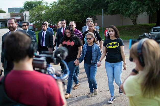 Rebecca Rodriguez, 15, Kimberly Rodriguez, 10, and Karen Rodriguez, 18, wearing Batman shirts lead their parents to the ICE headquarters in Houston so his father can be given further instructions about the 60-day extension the U.S. government. Monday, June 26, 2017, in Houston. Photo: Marie D. De Jesus, Houston Chronicle / © 2017 Houston Chronicle