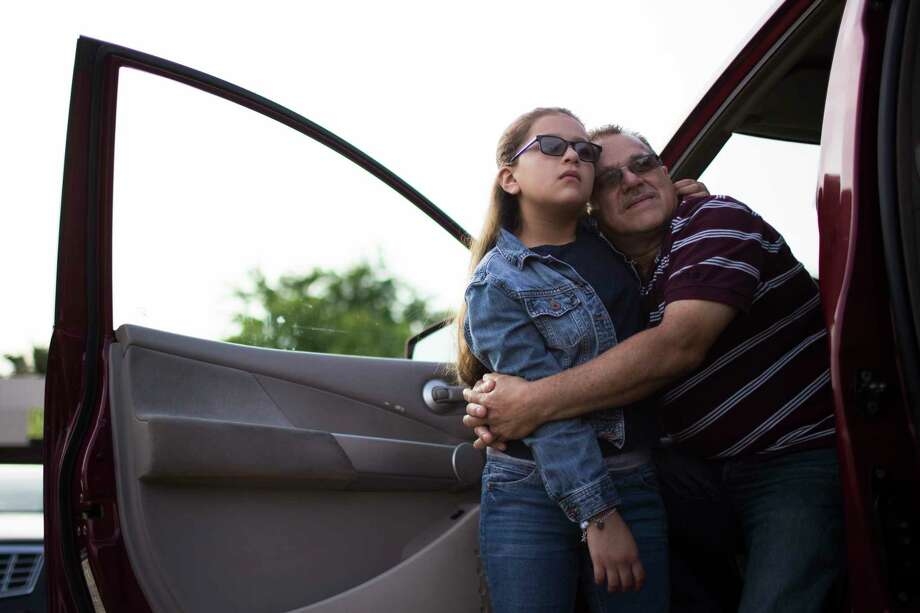 Juan Rodriguez rests on Kimberly Rodriguez's, 10,  shoulder as they wait to enter the ICE headquarters so Juan can present himself before the ICE officials for instruction on the conditions of the 60 days extension, Monday, June 26, 2017, in Houston. Photo: Marie D. De Jesus, Houston Chronicle / © 2017 Houston Chronicle