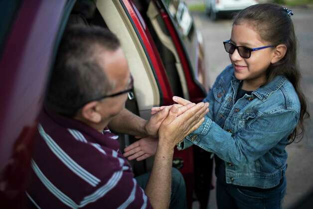 Juan Rodriguez and his daughter Kimberly Rodriguez, 10, play hand-clapping games while they wait to enter the ICE headquarters where  Rodriguez has been checking in with immigration officials for years and was allowed to stay in the country under prosecutorial discretion. This time, Juan has to present himself before the ICE officials for instruction on the conditions of the 60 days extension. Monday, June 26, 2017, in Houston. Photo: Marie D. De Jesus, Houston Chronicle / © 2017 Houston Chronicle