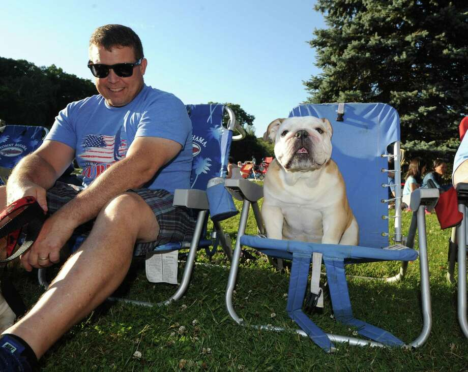 Jay Higgins of Stamford sits next to Daisy, an English Bulldog, during the Town of Greenwich 4th of July fireworks display and celebration at Binney Park in Old Greenwich, Conn., Saturday night, July 2, 2016. Photo: Bob Luckey Jr. / Hearst Connecticut Media / Greenwich Time