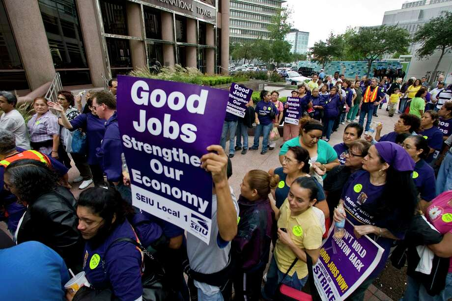 Union members hold up signs during a rally and march by members of SEIU (Service Employees International Union) along Louisiana Street Wednesday, Oct. 28, 2009, in Houston.