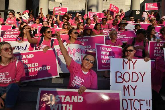 "Supporters and patients of Planned Parenthood take part in a ""Pink the Night Out"" rally at City Hall, which is part of a nationwide series of actions in support of the organization and in opposition to US President Donald Trump's health care proposal, in Los Angeles, California on June 21, 2017. / AFP PHOTO / Mark RALSTONMARK RALSTON/AFP/Getty Images"
