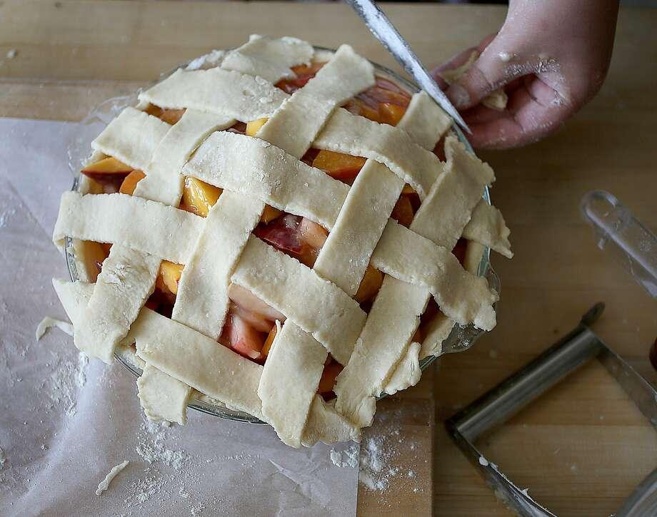 Elizabeth Simon of Revenge Pies makes a peach pie. Photo: Liz Hafalia, The Chronicle