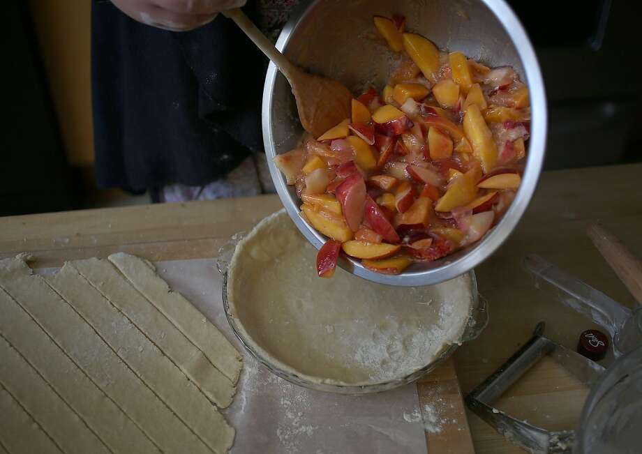 Adding peaches into the pie shell. Photo: Liz Hafalia, The Chronicle