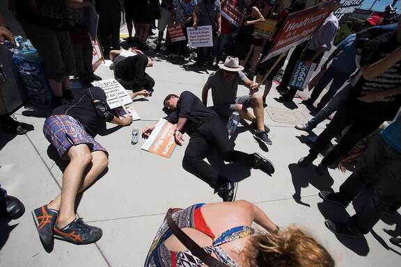 """People stage a """"die-in"""" during a rally in favor of single-payer healthcare for all Californians as the US Senate prepares to vote on the Senate GOP health care bill, outside the office of California Assembly Speaker Anthony Rendon, June 27, 2017 in South Gate, California.   Rendon announced last week that Senate Bill SB 562 - the high-profile effort to establish a single-payer healthcare system in California - would be shelved, saying it was """"incomplete.""""    / AFP PHOTO / Robyn BeckROBYN BECK/AFP/Getty Images"""