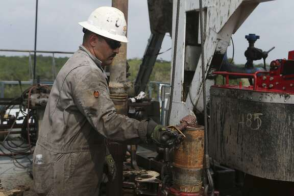 A roughneck at an Abraxas Petroleum site in South Texas' Eagle Ford Shale field lubricates a section of drilling pipe. Both service and exploration and production oil companies noted in a new Dallas Fed energy report that the future is uncertain as oil prices remain low.