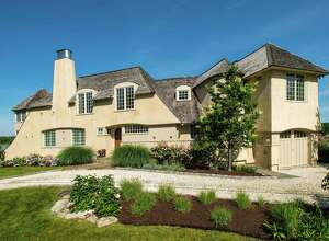 The award-winning stucco house at 32 Edgewater Hillside, enjoys 122 feet of direct water frontage on Old Mill Pond with panoramic views of Long Island Sound.