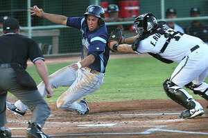 Corpus Christi baserunner George Springer slips around to the plate in the first inning, evading the tag by catcher Eddy Rodriguez as the Missions host the Hooks  on May 7, 2013.