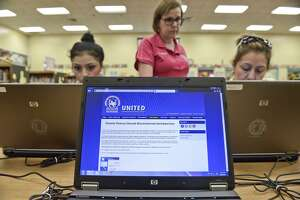 The login screen for the UISD registration website can be seen on a laptop, Tuesday afternoon as Admissions Specialist Lorena Meza helps Cristina Guerrero and Maria Guadalupe Guerrero login to the website at the Finely Elementary Library during open online registration.