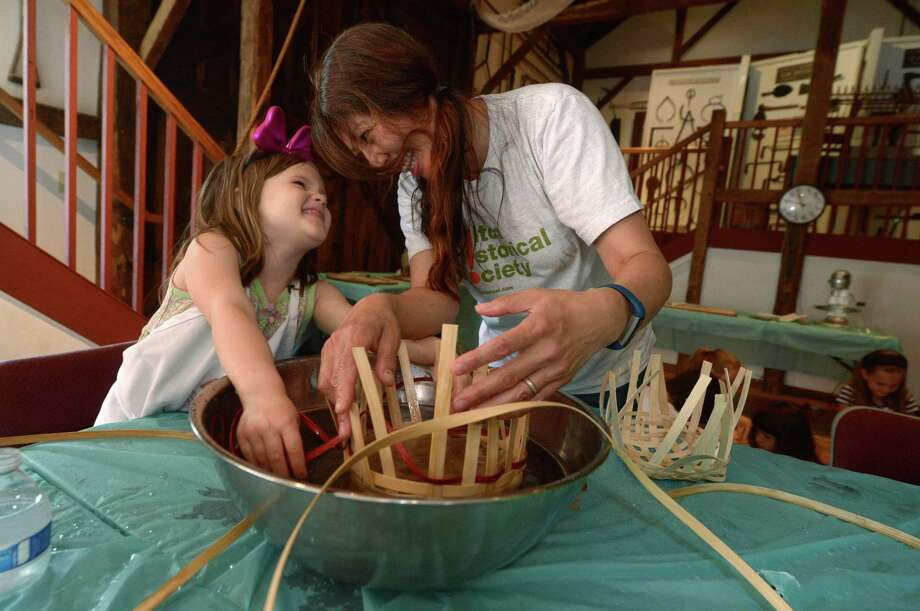 Lillian Corliss, 5, and Museum Educator Lola Chen share a laugh while weaving baskets during Colonial Boot Camp at the Wilton Historical Society Tuesday, June 27, 2017, in Wilton, Conn. The Wilton Historical Society offers week-long programs throughout the summer where children get a chance to take part in a variety of historical activities, including making bread and churning butter, soap making, tin punching, dying T-shirts with natural materials such as onion skins and woodworking. Photo: Erik Trautmann / Hearst Connecticut Media / Norwalk Hour