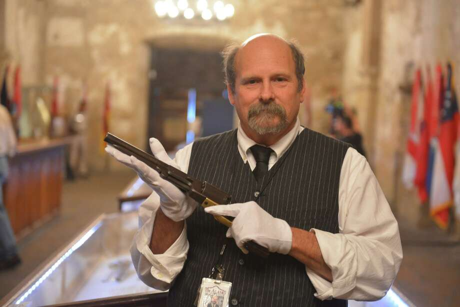 "Alamo historian and curator Dr. Bruce Winders displays the ""Firearms of the Texas Frontier, Flintlocks to Cartidge (1836-1876) which was on display in the Alamo Shrine in 2015. He is holding a Colt Walker pistol. Photo: Express-News File Photo"