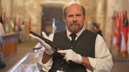 """Alamo historian and curator Dr. Bruce Winders displays the """"Firearms of the Texas Frontier, Flintlocks to Cartidge (1836-1876) which was on display in the Alamo Shrine in 2015. He is holding a Colt Walker pistol."""