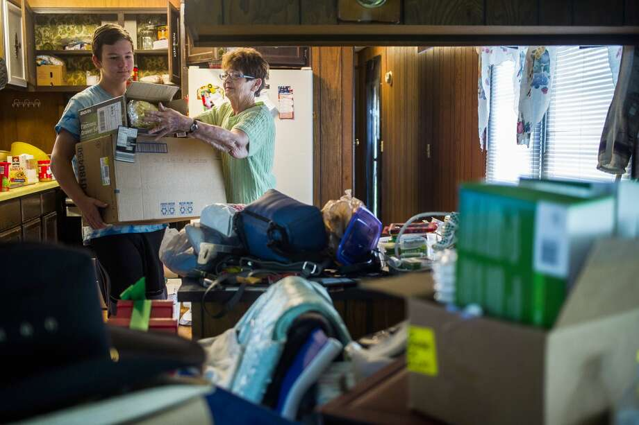 Shirley Albach, right, hands boxes of salvageable food items to her grandson, Cameron Navarro, 14, as Navarro helps Albach clear out the mobile home she shares with her husband Harry on Wednesday in Alpine Mobile Home Park. Photo: (Katy Kildee/kkildee@mdn.net)