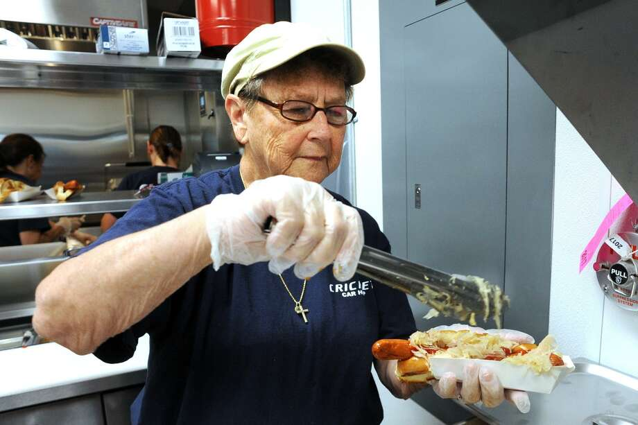 Pat Fogg, who worked at the original Cricket Car Hop, dresses a hotdog with sauerkraut at the new Cricket Car Hop, in Stratford, Conn. June 28, 2017. Photo: Ned Gerard / Hearst Connecticut Media / Connecticut Post