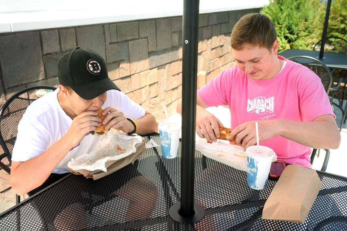 Dan Decilio, with a hamburger, and Jeff Sharnick, with a foot-long hotdog, were two of the first customers to visit the new Cricket Car Hop, in Stratford, Conn. June 28, 2017.