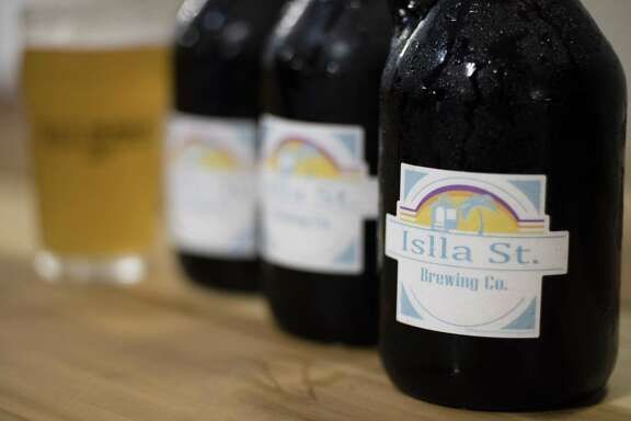 Islla St. Brewing Co. growlers line the table for sampling.