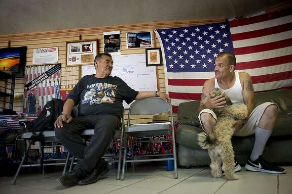 Deported U.S. military veterans Andy de Leon, left, and Alejandro Gomez Cortez chat at the Deported Veterans Support House in Tijuana.