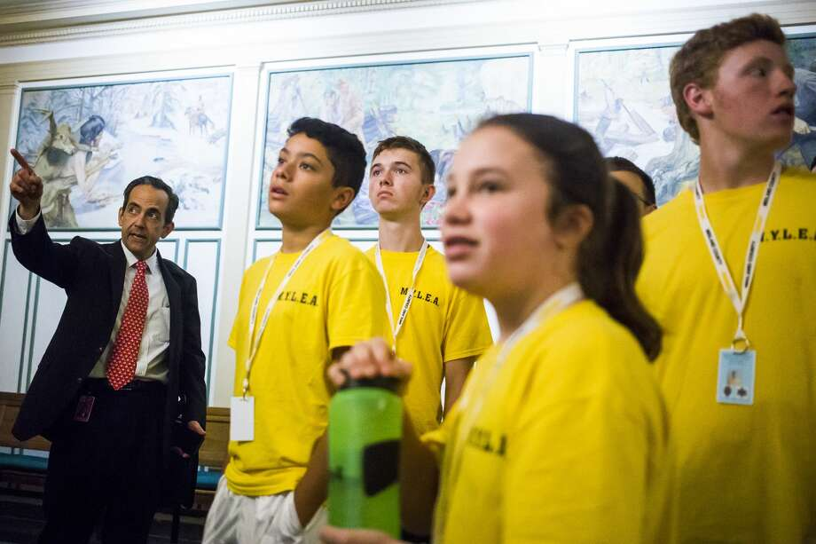 Circuit Court Judge Stephen Carras points out murals inside the Midland County Courthouse to, from left to right, Brendon Redwantz, 14, Austin West, 14, Madalynn Bartlett, 13, and Caleb Brenske, 14, all participants in the Midland Youth Law Enforcement Academy, on Tuesday. Photo: (Katy Kildee/kkildee@mdn.net)