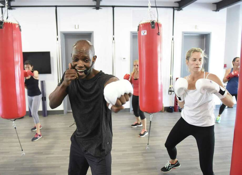 Trainer Jonathan Edmond coaches Kolleen Evers, of Old Greenwich, and others through a boxing workout at Belly and Body gym in Old Greenwich, Conn. Wednesday, June 28, 2017. The new gym provides boxing classes taught by trainer Jonathan Edmond split into three 15-minute rounds - cardio functional movements and boxing, followed by strength and speed stations. Photo: Tyler Sizemore / Hearst Connecticut Media / Greenwich Time