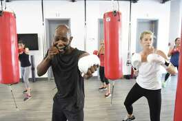 Trainer Jonathan Edmond coaches Kolleen Evers, of Old Greenwich, and others through a boxing workout at Belly and Body gym in Old Greenwich, Conn. Wednesday, June 28, 2017. The new gym provides boxing classes taught by trainer Jonathan Edmond split into three 15-minute rounds - cardio functional movements and boxing, followed by strength and speed stations.