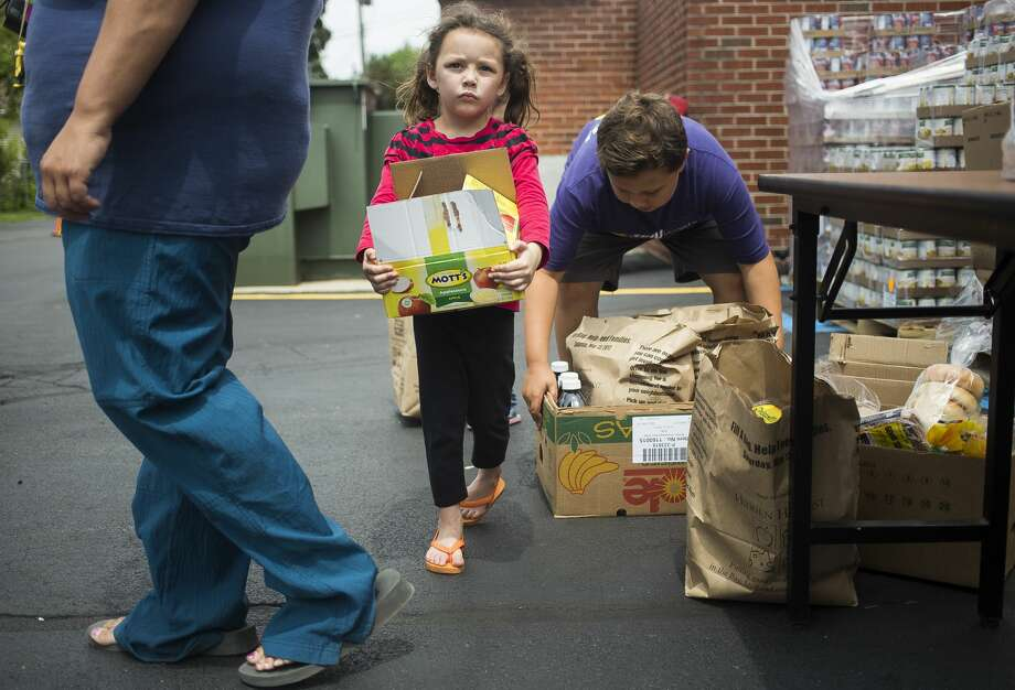 Destiny Lown, 5, center, and Tejshun Willman, 10, right, carry boxes of free food items to their car at a relief site for flood recovery assistance on Wednesday, June 28, 2017 at the Midland County ESA building, 3917 Jefferson Ave. Photo: (Katy Kildee/kkildee@mdn.net)