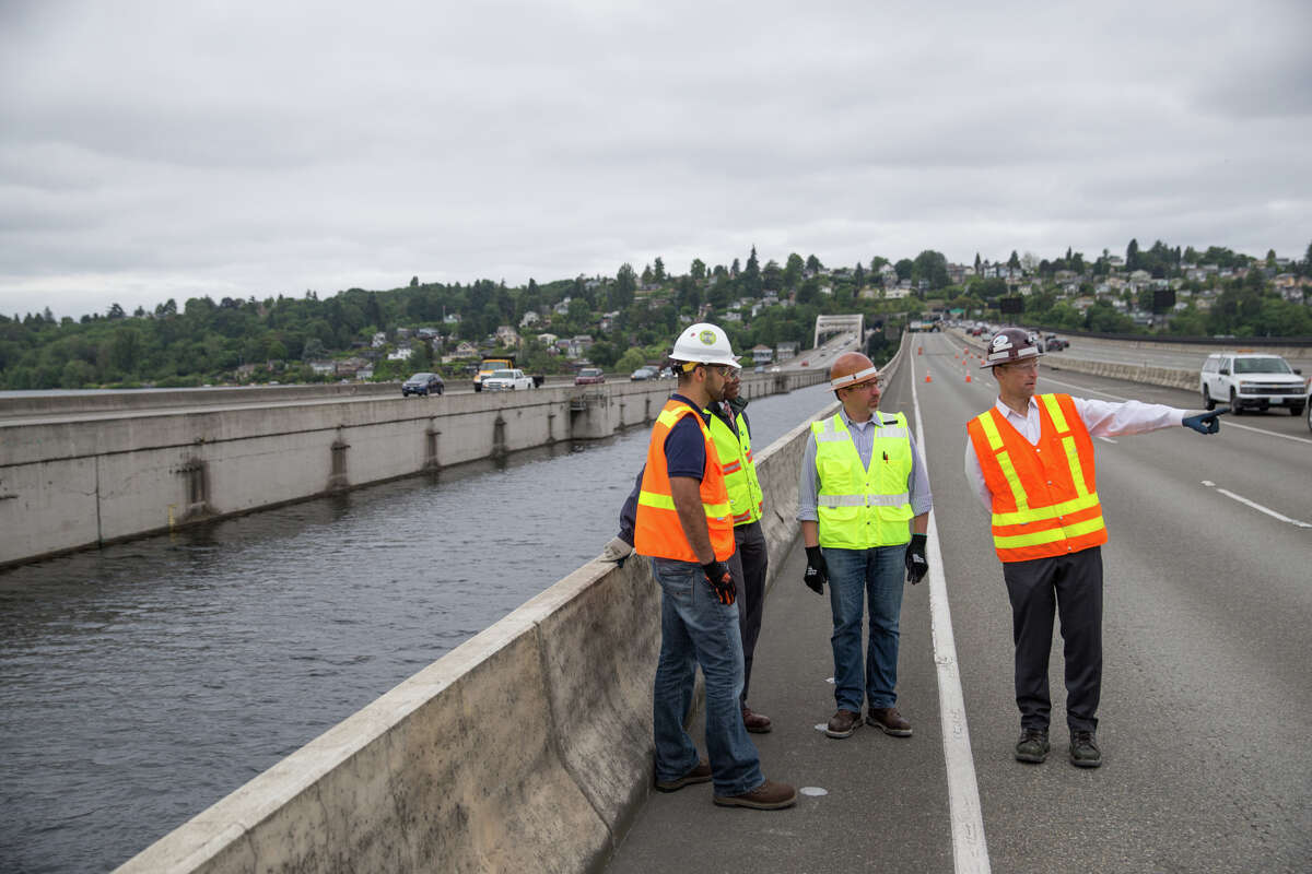 Chief Executive Officer of Sound Transit, Peter Rogoff, and other project managers talk on the closed, center, public transportation lane of the I-90 bridge on Wednesday, June 28, 2017.