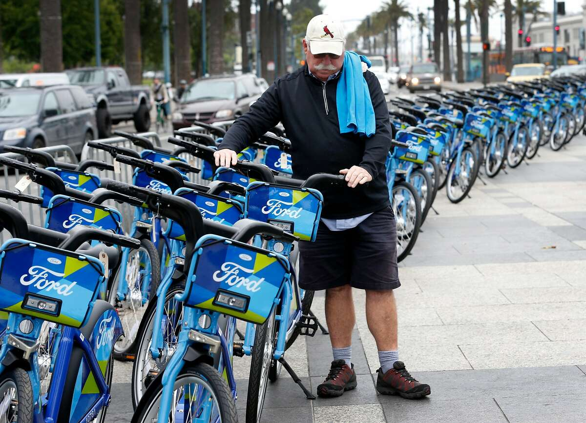 Michael Corcoran, a regular user of shared bicycles, checks out the Ford GoBike fleet in front of the Ferry Building in San Francisco, Calif. on Wednesday, June 28, 2017. The Bay Area-wide bike sharing service, which plans a fleet of 3,500 bicycles by Labor Day and as many as 7,000 by the end of 2018, went into service today.