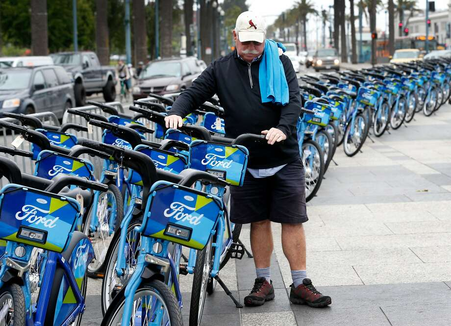 Michael Corcoran, a regular user of shared bicycles, checks out the Ford GoBike fleet in front of the Ferry Building in San Francisco, Calif. on Wednesday, June 28, 2017. The Bay Area-wide bike sharing service, which plans a fleet of 3,500 bicycles by Labor Day and as many as 7,000 by the end of 2018, went into service today. Photo: Paul Chinn, The Chronicle