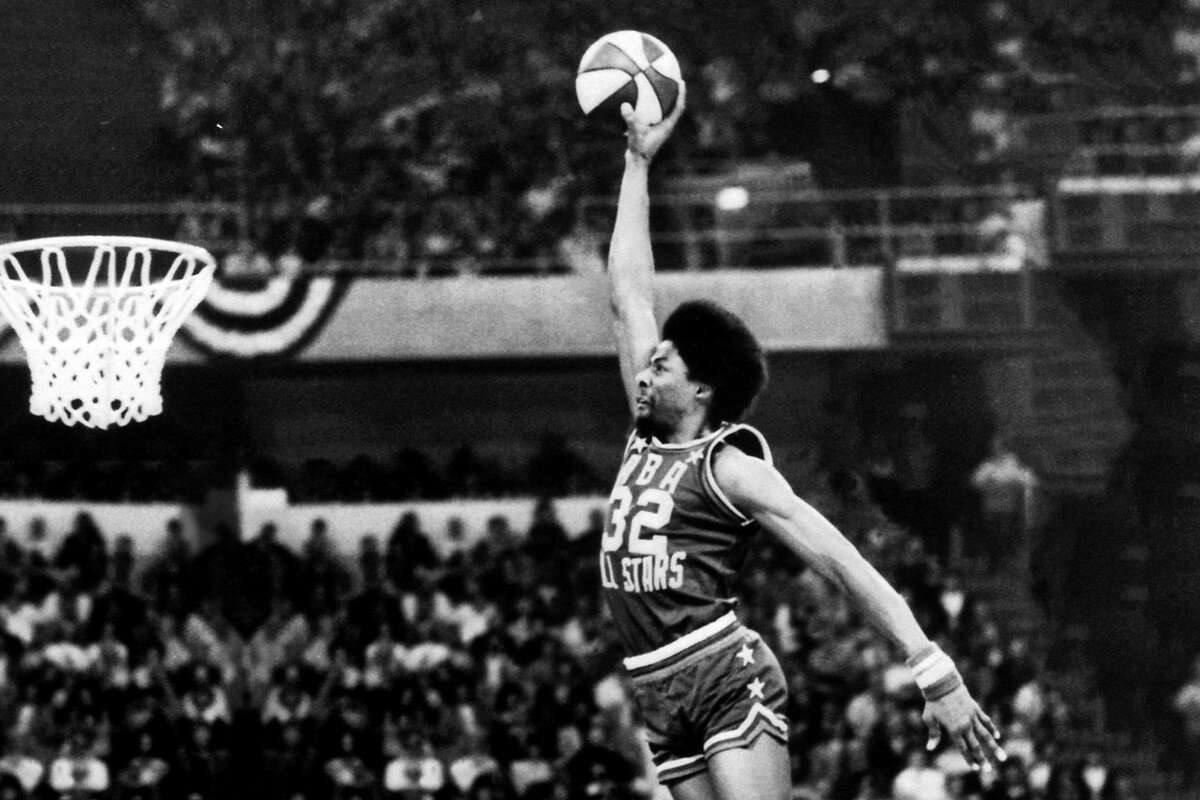 """Julius """"Dr. J"""" Erving of the ABA New York Nets goes for a dunk from the free throw line during the inaugural Slam Dunk Contest during halftime at the 9th ABA All-Star Game on Jan. 27, 1976, at McNichols Arena in Denver, Colo."""